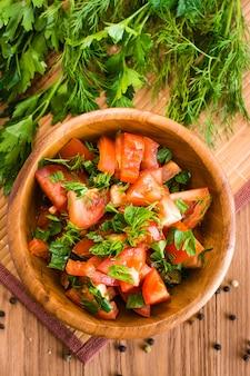 Salade gemaakt van tomaten en verse kruiden in houten plaat. bovenaanzicht