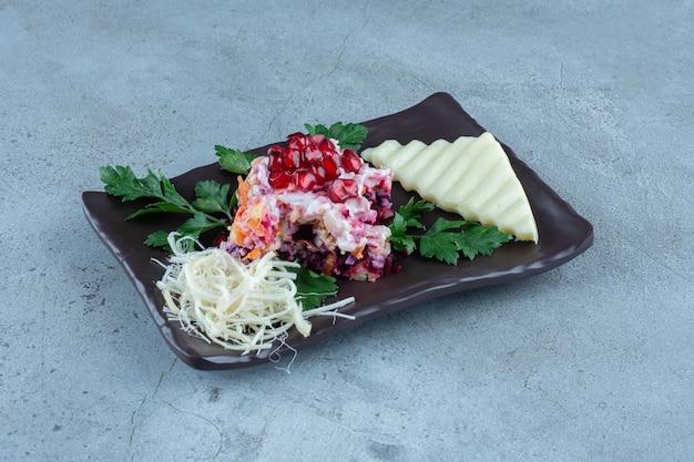 Salade geserveerd met gesneden en geraspte kaas op een zwarte schotel op marmer.