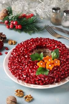 Salade granaatappelarmband versierd met granaatappelpitjes en wortelbloemen op een lichtblauwe tafel. de feestelijke salade van traditioneel russisch nieuwjaar, close-up, verticaal formaat