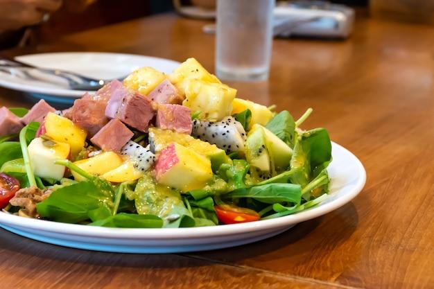 Salade groente- en fruitmix met ham op houten tafel.