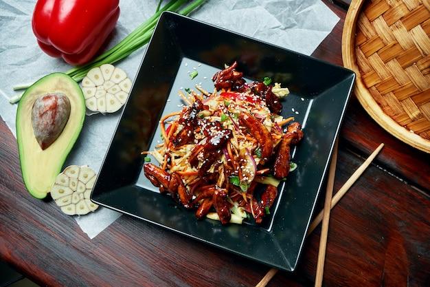 Salade in aziatische stijl - fijngehakte wortelen, kool en paprika met honing-mosterddressing en wokkip in teriyakisaus in zwarte plaat op houten tafel. detailopname. straatvoedsel