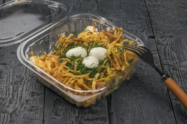 Salade in de vorm van een nest in een container voor veilige levering