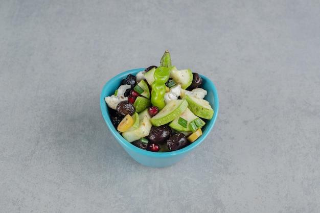 Salade in een blauwe kop met gemengde gehakte groente en fruit.