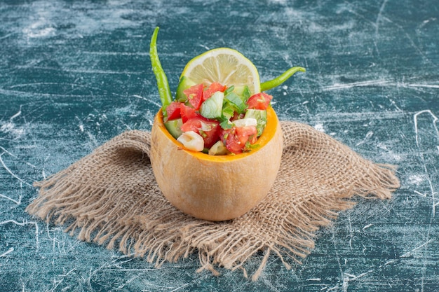 Salade in een gesneden pompoen met gemengde ingrediënten.