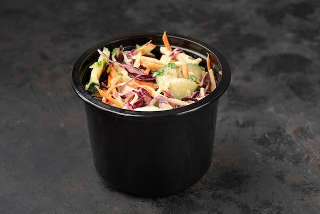 Salade in plastic bak afhaalmaaltijden salades op een donkere stenen ondergrond met copyspace. snelle levering van eten. close-up voor menu