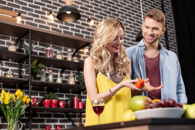 Salade koken. blondharige aantrekkelijke vrolijke vrouw die lacht terwijl ze kleine tomaat snijdt voor salade