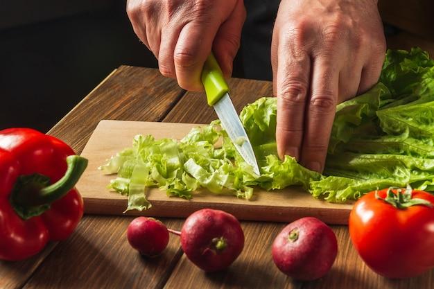 Salade koken in de keuken van het restaurant chef is handen close-up gesneden salade greens