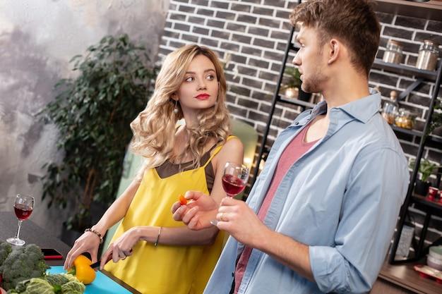 Salade koken. krullende blonde vrouw kijkt naar haar vriendje terwijl ze salade kookt voor een romantisch diner met wijn