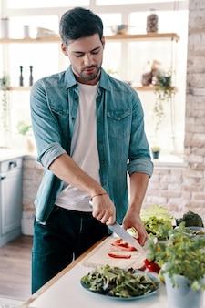 Salade maken. knappe jongeman in vrijetijdskleding die groenten snijdt terwijl hij thuis in de keuken staat