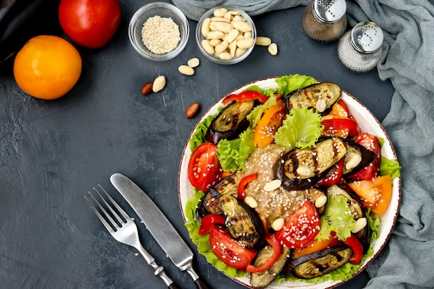 Salade met aubergine, tomaat, paprika, sla, sesam en pinda's, bovenaanzicht op donker,