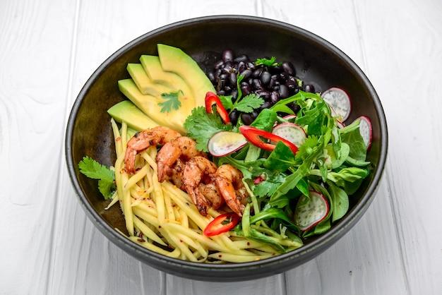 Salade met avocado en garnalen in kom, bovenaanzicht. gezond eten