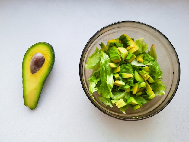 Salade met avocado en sesamzaadjes, olie wordt gegoten, op een houten. avocadosalade in een plaat, vegetarisch voedsel, groene dieetsalade.