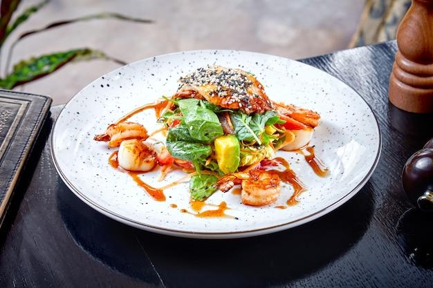 Salade met avocado, garnalen, spinazie en kipfilet in zoetzure saus. warme gegrilde salade op een witte plaat. restaurant eten achtergrond. schoon eten, dieet concept. zeevruchten