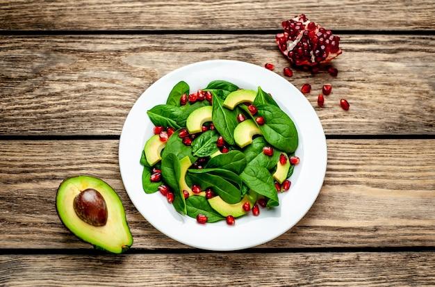 Salade met avocado, rucola, spinazie, granaatappel, zaden op houten achtergrond