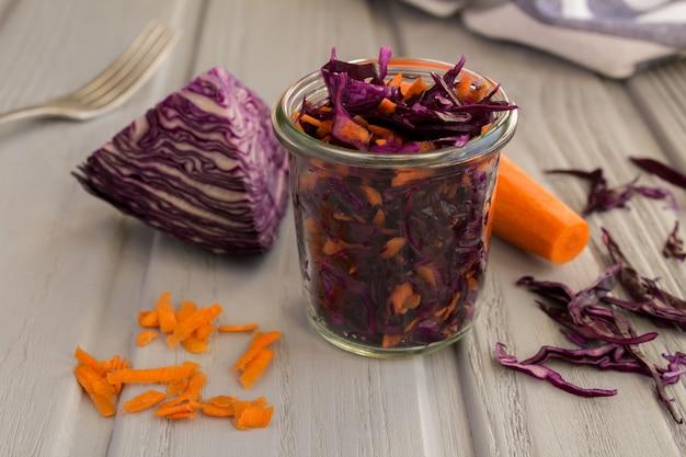Salade met blauwe kool en wortel in de glazen pot op de grijze houten achtergrond