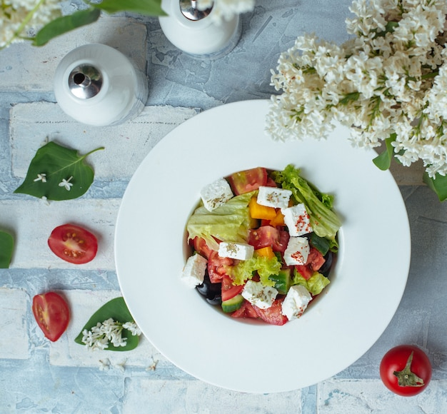 Salade met blokjes groente en witte kaas.