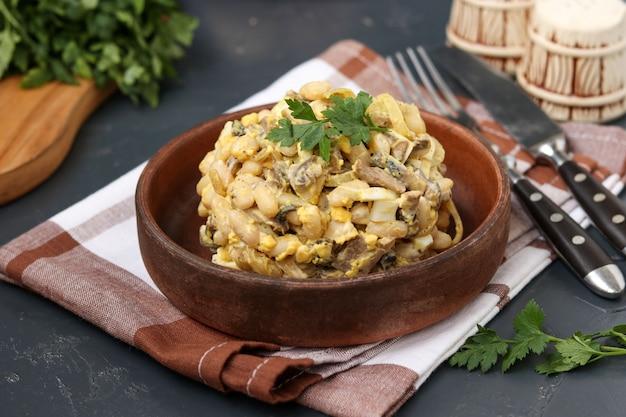 Salade met bonen, peterselie en champignons in een bruine kom op een donkere ondergrond