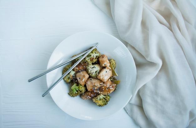 Salade met broccoli en kip. hete salade in de saus geserveerd in een witte plaat. aziatische stijl schotel. licht.
