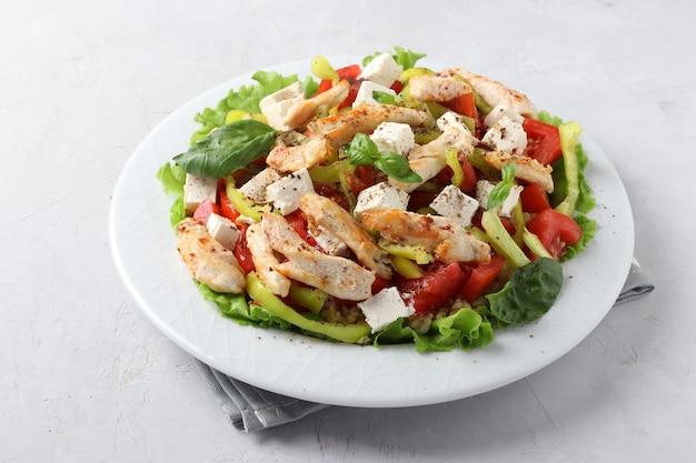 Salade met bulgur, gebakken kip, paprika, basilicum en feta op een witte plaat, close-up. horizontaal formaat