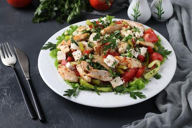 Salade met bulgur, gebakken kip, paprika, basilicum en feta op witte plaat op donkere achtergrond, close-up. horizontaal formaat