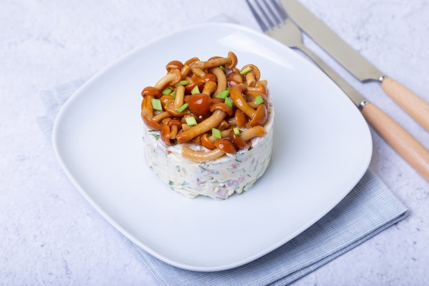 Salade met champignons (honingzwam), ham, aardappelen, kaas en mayonaise. de traditionele russische mand van de saladepaddestoel bast. selectieve focus, close-up.