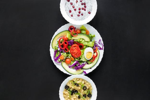 Salade met chia-zaadpudding en gezonde haver op een rij gerangschikt