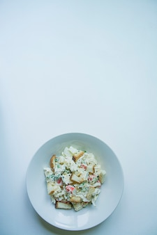 Salade met crackers, krabsticks, kipfilet, verse groenten en harde kaas