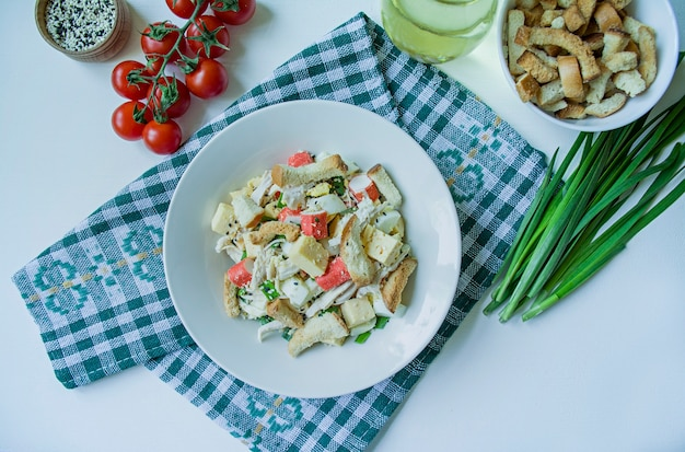 Salade met crackers, krabsticks, kipfilet, verse kruiden en harde kaas