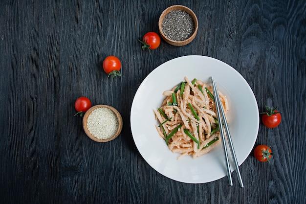 Salade met daikon radijs, groene uien, honing en rode chilipoeder. aziatische salade. plat leggen. . donker