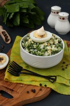 Salade met daslook, eieren en mayonaise in een witte kom op een houten bord