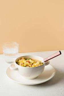 Salade met ditalini pasta, erwten, veganistische worst op moderne witte tafel. detailopname.