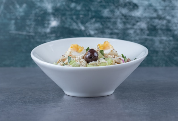 Salade met eieren en in blokjes gesneden kip in witte kom.