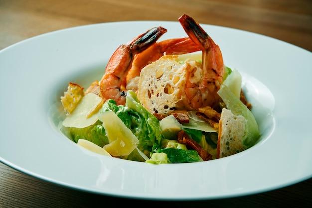 Salade met garnalen, parmezaan, sla en croutons. caesar zeevruchtensalade in een witte kom op een houten lijst. gezond eten en gezond tussendoortje. detailopname. selectieve aandacht.
