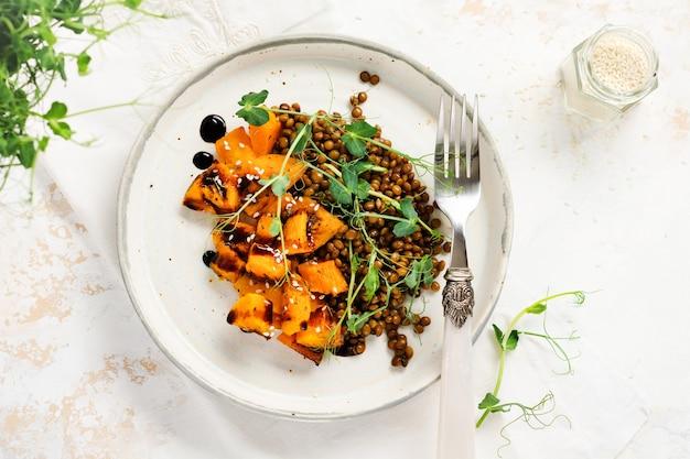Salade met gebakken pompoen, linzen en balsamico dressing gegarneerd met erwten microgreens op een lichtje
