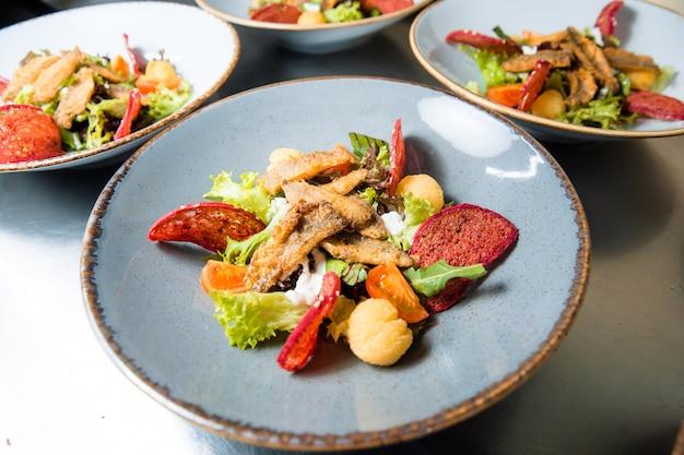 Salade met gebakken visfilet rode mul. malse lamsfilet gebakken in maïsmeel, verse kruiden, cherry tomaten