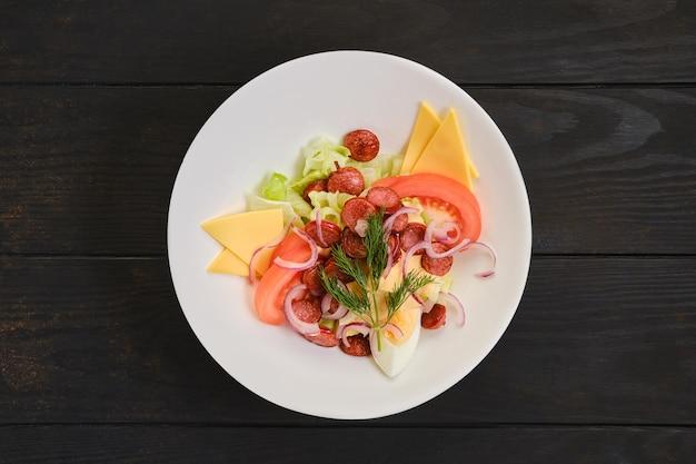 Salade met gebakken worst, tomaat, gekookt ei, rode ui en cheddar