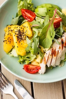 Salade met gegrilde kip, mango, sla, avocado, tomaten, rucola, kaas saus op een witte plaat