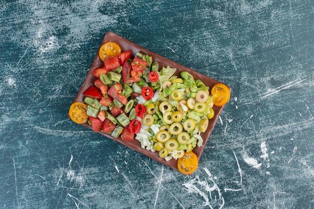 Salade met gehakte kerstomaatjes, sperziebonen en kool.