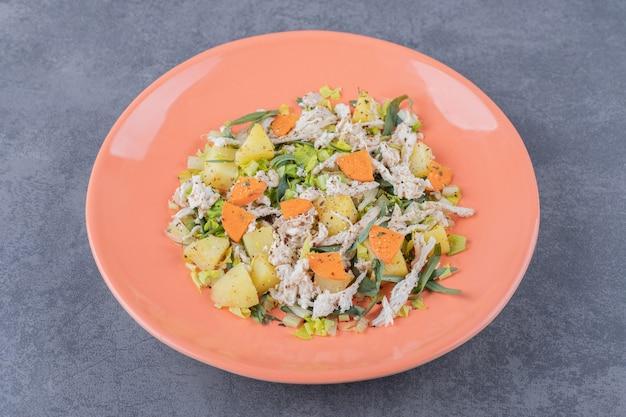 Salade met gehakte kip op oranje plaat.