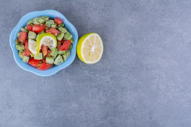 Salade met gehakte tomaat en sperziebonen geserveerd met citroen