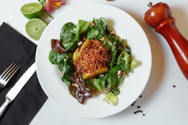 Salade met gekarameliseerde lever en couscous. salademix, gekarameliseerde kippenlever met appels, couscous, frambozensaus, aardappeltaart, walnoot