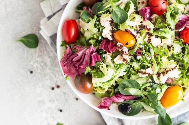 Salade met gemengde slablaadjes, cherrytomaten, ricotta en balsamico