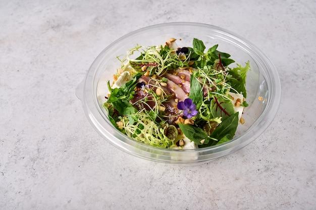 Salade met gerookte eendenborst, groenten, kaas en kruiden in een transparant bakje designer food