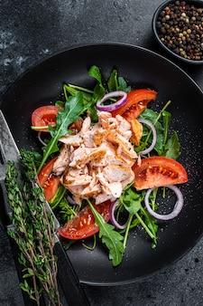 Salade met geroosterde zalmfilet steak, verse salade rucola en tomaat in een bord. zwarte achtergrond. bovenaanzicht.