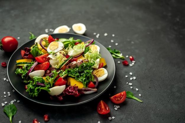 Salade met granaatappel, tomaten, verse komkommers, uien, sesamzaadjes en cashewnoten, kruiden op een stenen achtergrond. gezond vegetarisch eten.