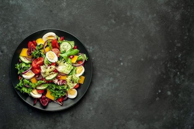 Salade met granaatappel, tomaten, verse komkommers, uien, sesamzaadjes en cashewnoten, kruiden op een stenen achtergrond met kopie ruimte voor uw tekst