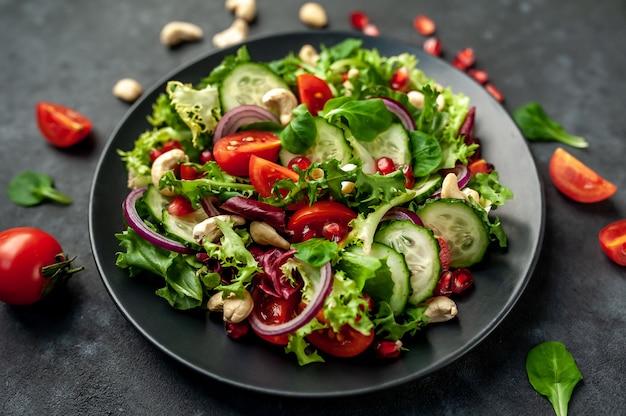 Salade met granaatappel, tomaten, verse komkommers, uien, sesamzaadjes en cashewnoten