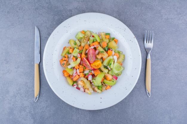 Salade met groene groente en cherrytomaatjes in keramische gerechten