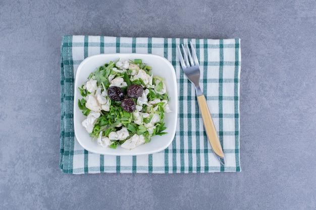 Salade met groene kruiden, bloemkool en zwarte olijven
