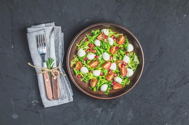 Salade met groene slamix geserveerd op een bruine keramische plaat